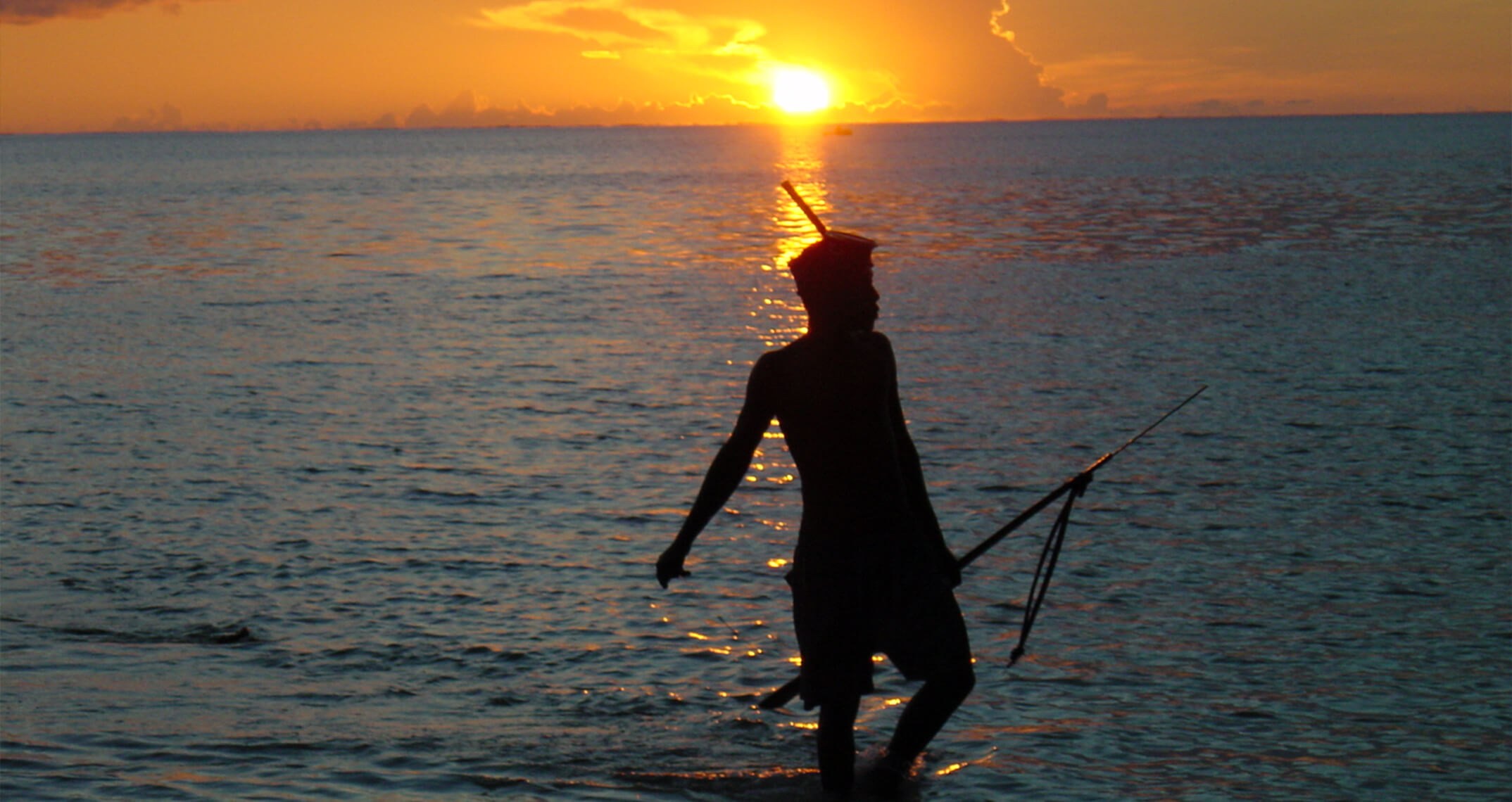 Man standing in the ocean at sunset.